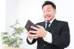 財布を見て驚くビジネスマンの写真素材 [FYI04708845]