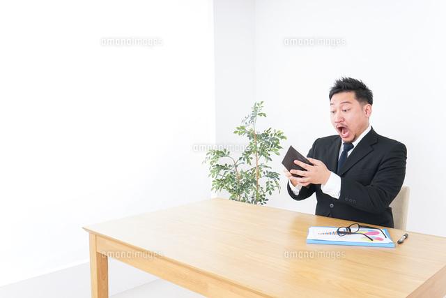 財布を見て驚くビジネスマンの写真素材 [FYI04708846]