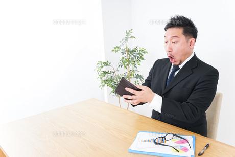 財布を見て驚くビジネスマンの写真素材 [FYI04708847]