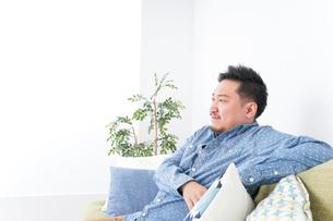 家でリラックスをする男性の写真素材 [FYI04708854]