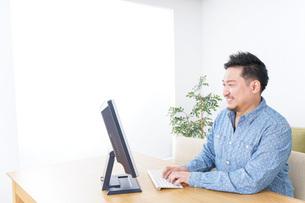 家でパソコンを使う男性の写真素材 [FYI04708901]
