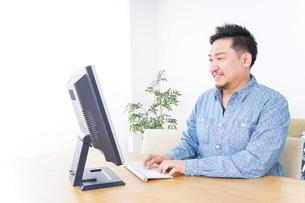 家でパソコンを使う男性の写真素材 [FYI04708903]