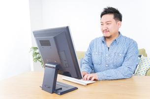 家でパソコンを使う男性の写真素材 [FYI04708905]