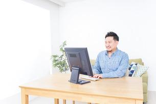 家でパソコンを使う男性の写真素材 [FYI04708907]