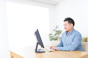 家でパソコンを使う男性の写真素材 [FYI04708908]