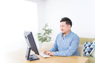 家でパソコンを使う男性の写真素材 [FYI04708909]