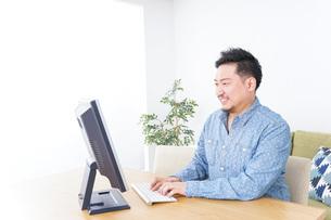 家でパソコンを使う男性の写真素材 [FYI04708910]