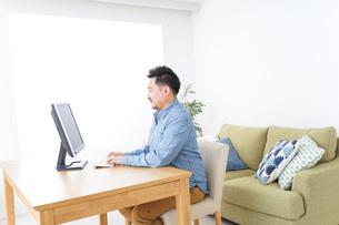家でパソコンを使う男性の写真素材 [FYI04708911]