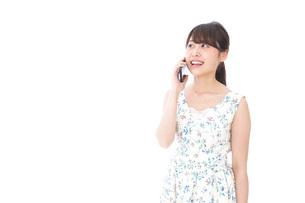 スマホで通話をする若い女性の写真素材 [FYI04709106]