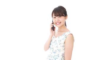 スマホで通話をする若い女性の写真素材 [FYI04709120]