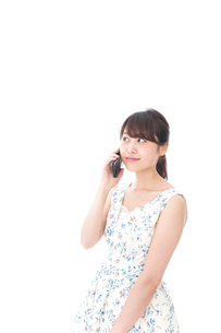 スマホで通話をする若い女性の写真素材 [FYI04709121]