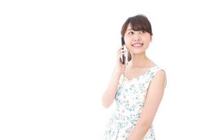 スマホで通話をする若い女性の写真素材 [FYI04709123]