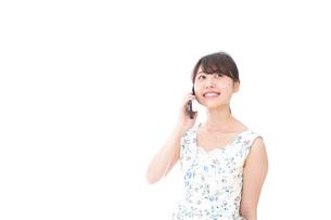 スマホで通話をする若い女性の写真素材 [FYI04709129]