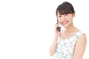 スマホで通話をする若い女性の写真素材 [FYI04709134]
