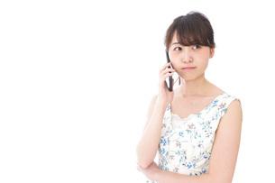 スマホで通話をする若い女性の写真素材 [FYI04709141]