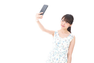 スマホを使う若い女性の写真素材 [FYI04709143]