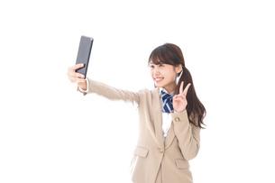 自撮りをする制服姿の学生の写真素材 [FYI04709612]