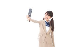 自撮りをする制服姿の学生の写真素材 [FYI04709627]