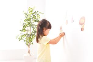 シールを貼る子どもの写真素材 [FYI04710195]