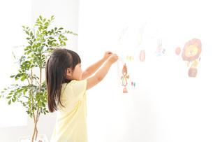 シールを貼る子どもの写真素材 [FYI04710207]