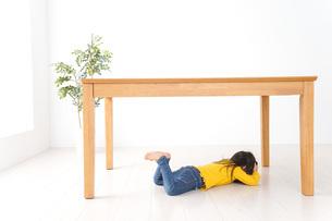 机の下に避難する子どもの写真素材 [FYI04710956]