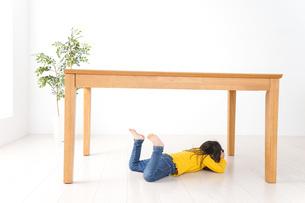 机の下に避難する子どもの写真素材 [FYI04710957]