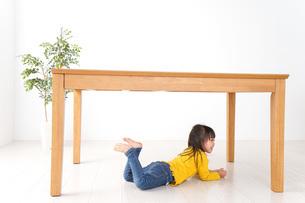 机の下に避難する子どもの写真素材 [FYI04710958]