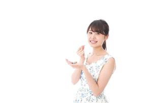 お菓子を食べる若い女性の写真素材 [FYI04711352]