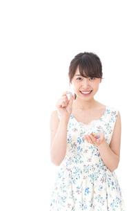 お菓子を食べる若い女性の写真素材 [FYI04711353]