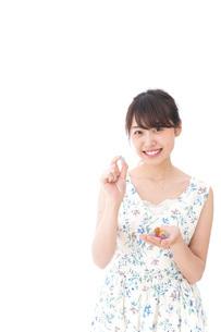 お菓子を食べる若い女性の写真素材 [FYI04711354]
