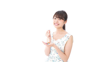 お菓子を食べる若い女性の写真素材 [FYI04711355]