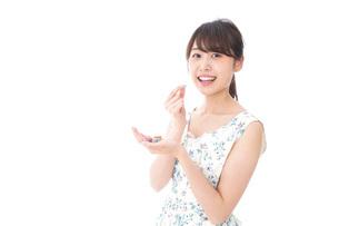 お菓子を食べる若い女性の写真素材 [FYI04711358]