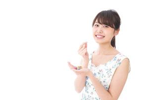 お菓子を食べる若い女性の写真素材 [FYI04711359]