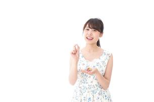 お菓子を食べる若い女性の写真素材 [FYI04711360]