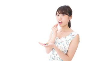 お菓子を食べる若い女性の写真素材 [FYI04711362]
