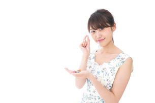 お菓子を食べる若い女性の写真素材 [FYI04711365]