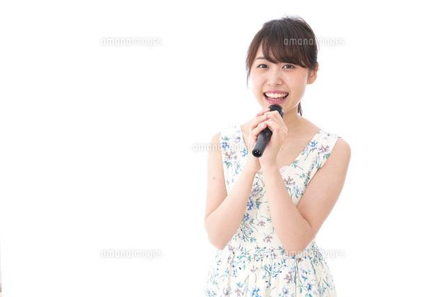 カラオケで歌を歌う若い女性の写真素材 [FYI04711379]