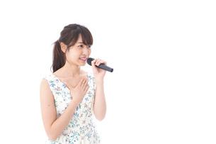 カラオケで歌を歌う若い女性の写真素材 [FYI04711387]
