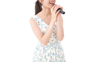 カラオケで歌を歌う若い女性の写真素材 [FYI04711389]