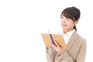 考えながら書く女性の写真素材 [FYI04711687]
