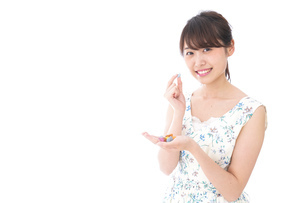 お菓子を食べる若い女性の写真素材 [FYI04711761]