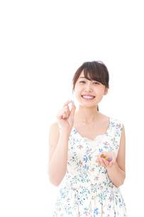 お菓子を食べる若い女性の写真素材 [FYI04711767]