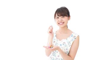 お菓子を食べる若い女性の写真素材 [FYI04711769]