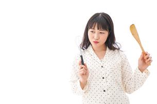 エプロンを着てごはんを作る若い女性の写真素材 [FYI04711885]