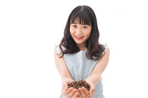 コーヒー豆を持つ若い女性の写真素材 [FYI04711908]