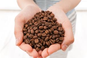 コーヒー豆を持つ若い女性の写真素材 [FYI04711917]