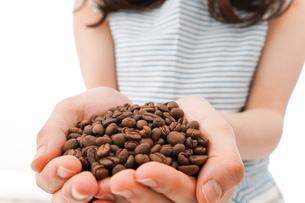 コーヒー豆を持つ若い女性の写真素材 [FYI04711918]