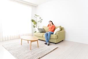 家でテレビを見る女性の写真素材 [FYI04712018]