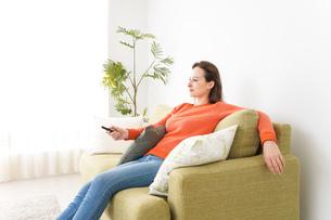 家でテレビを見る女性の写真素材 [FYI04712021]