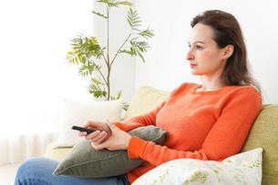 家でテレビを見る女性の写真素材 [FYI04712041]